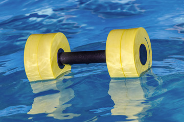 A yellow dumbbell for water aerobics lies in the water. Sport.