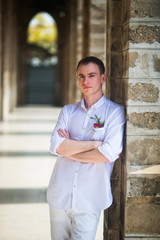 Portrait of the groom in a white shirt near the stone columns of the Catholic Church