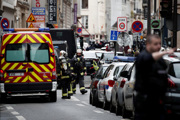 French police and firefighters secure the street as a man has taken two people hostage at a business in Paris
