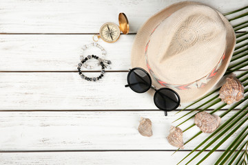 Composition with tourist's stuff on wooden background, top view