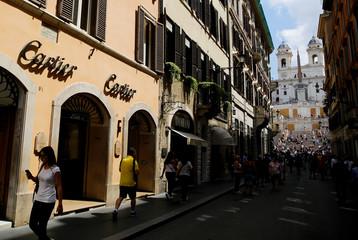 Tourists walk in Via dei Condotti street in downtown Rome