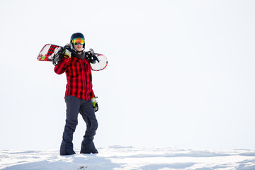 Photo of man with snowboard on shoulders standing on snowy mountainside