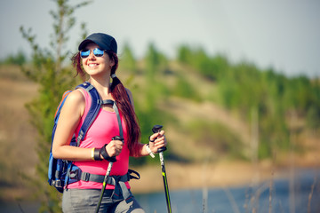 Image of young athletic girl with walking sticks on background of lake and green vegetation