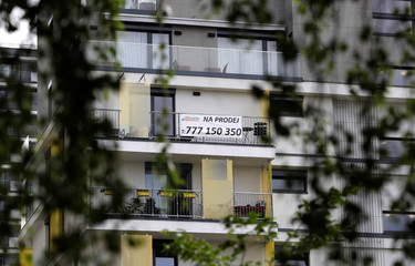 """A real estate """"For Sale"""" sign is seen hanging outside an apartment building in Prague"""