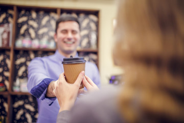 Photo of barista man stretching glass to woman on blurred background.
