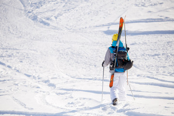 Photo from back of sports woman with skis and sticks in winter