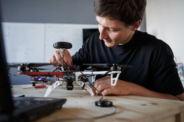 Photo of young man cleaning quadrocopter at table