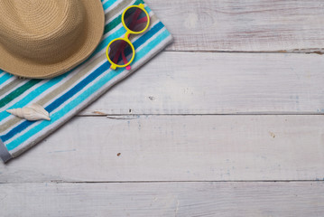 Hats, sunglasses, beach shoes, towels on the board