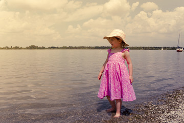 A little girl wearing a sunhat is walking in the water