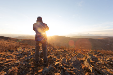 man take photo on top of mountain with sunrise