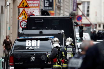 French police and special police forces (BRI) secure the street as a man has taken people hostage at a business in Paris