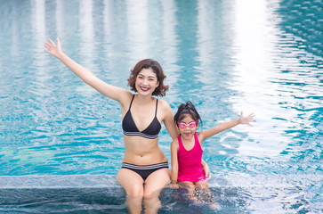 mother and daugther love to swim together on swimming pool.