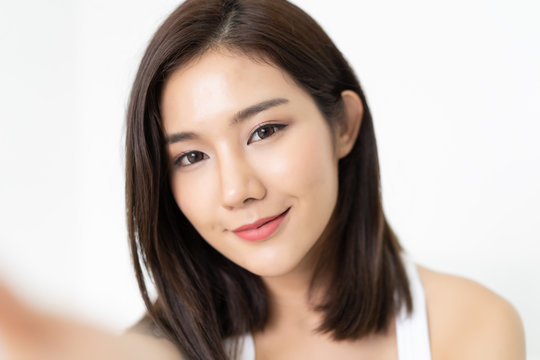 Close-up of young Asian beautiful woman taking selfie. Isolated white background