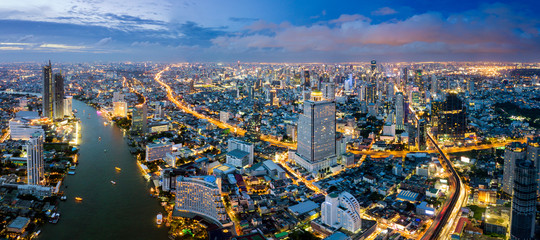 Fototapete - Aerial view of Bangkok skyline and skyscraper with BTS skytrain Bangkok downtown. Panorama of Sathorn and Silom business district Bangkok Thailand at night.
