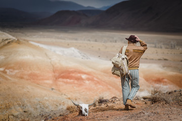 Beautiful young girl in hare, hat and with backpack travels among sands in wild