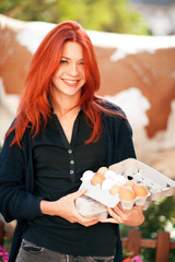 beautiful young woman buying fresh eggs at a farm, sustainable agriculture concept
