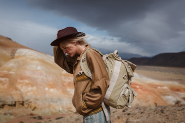 Portrait иeautiful young girl in hare, hat and with backpack travels among sands in wild