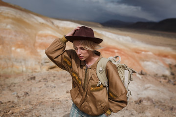Portrait beautiful young girl in hare, hat and with backpack travels among sands in wild
