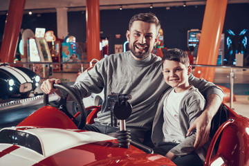 Happy smiling father and son sitting on toy car