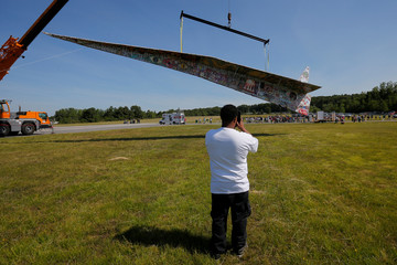 The Revolving Museum's 64-plus foot long paper airplane is suspended from a crane in Fitchburg