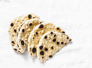 Homemade whole grain tortillas on a light background, top view