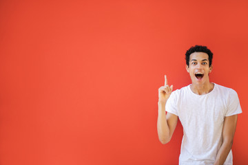 Excited young man pointing up his finger