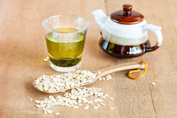 Oats flakes in wood spoon with hot green tea on wood table