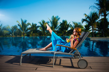 Young girl in blue dress posing on a lounger by the pool
