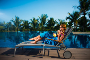A young girl in a blue dress lying on a lounger by the pool and drinking yellow juice