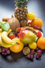 Assortment of Fresh Tropical and Summer Seasonal Fruits Pineapple Papaya Mango Coconut Oranges Kiwi Bananas Lemons Grapefruit Strawberries on Black Wet Background. Superfoods Antioxidants Vitamins