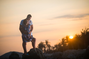 Guy hugs girl at sunset in the rocks in the tropics