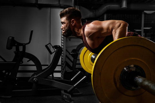 Young athlete lifts barbell to his chest. Concept workout