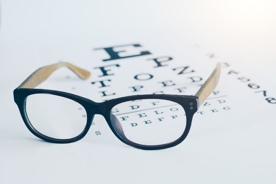 Eyeglasses on an optician visual text chart with white background. Eyesight optician concept