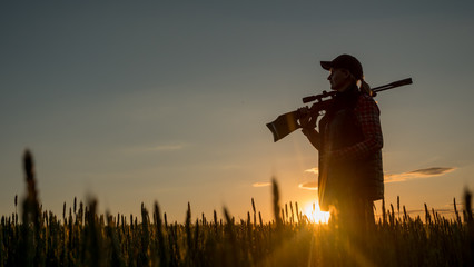 Fototapeta Silhouette of woman hunter. It stands in a picturesque place with a gun at sunset. Sports shooting and hunting concept