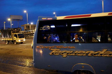 A boy travels on a bus along a road ahead of the second round of presidential in Bogota