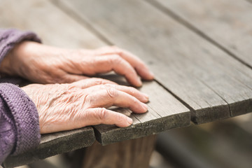 Old wrinkled female hands on a wooden table