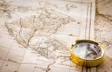 Explorer gold compass placed on a stack of very old geographical maps of North America and the United States.