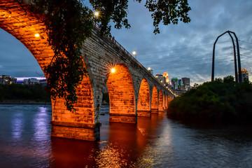 Poster Bridge historic stone arch bridge by the river at night