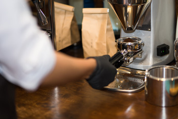 Close-up image of female barista using coffee-making machine making of espresso pouring from coffee machine. Professional coffee brewing
