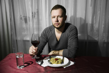 A man drinks wine and eats pasta