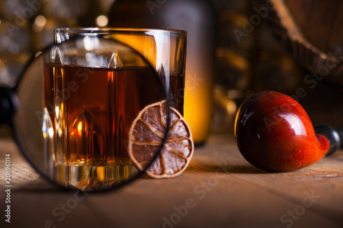 Glass of whiskey, magnifying glass, lemon and smooking pipe