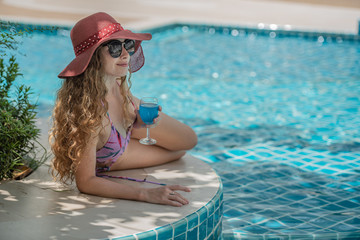 Beautiful long blonde wavy hair style woman model in bikini and sunglasses with cocktail at swimming pool.