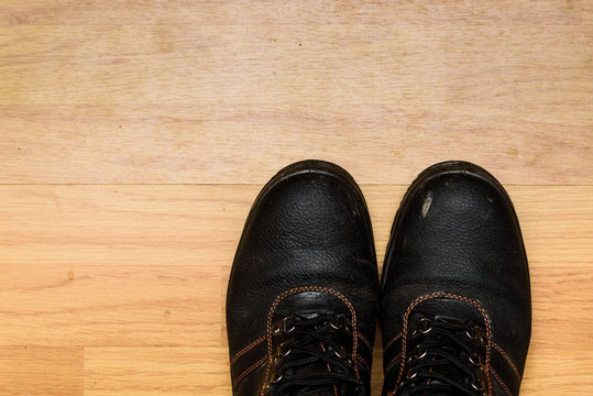 A pair of dirty used steel toe cap working boots isolated on a laminated wooden floor