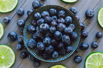 Centered Bowl of Blueberries with Scattered Berries and Sliced Limes