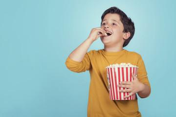 niño con palomitas de maíz sobre fondo azul