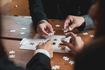 Group of Business people holding piece of jigsaw puzzle to solution problem on wooden table.Professional Businessman and Partnership meeting in office.Teamwork Business and partnership Concept.
