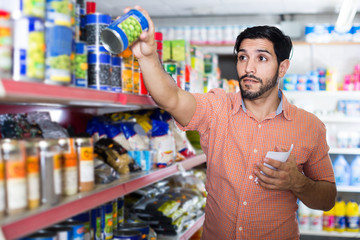 Man is choosing conserved peas using note list in supermarket.