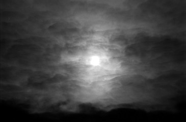 Dramatic cloudy sky in grayscale on film. Overcast weather and sun through cumulus clouds. Monochrome atmospheric dark scanned analog photography with grain and scratch. Lomography of nature.