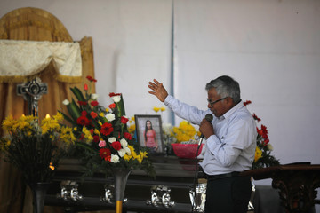 A man speaks during the funeral of 17-year-old Aura Yolanda Perez Paz, who died during the eruption of the Fuego volcano in Alotenango