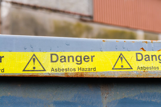 Warning tape across a bin at an Asbestos clean-up